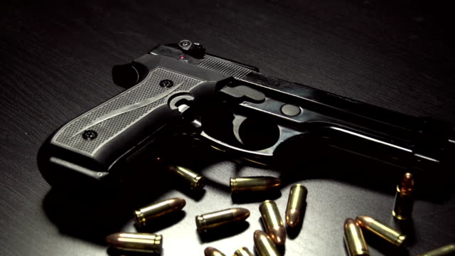 Dolly shot of 9 mm handgun with bullets video