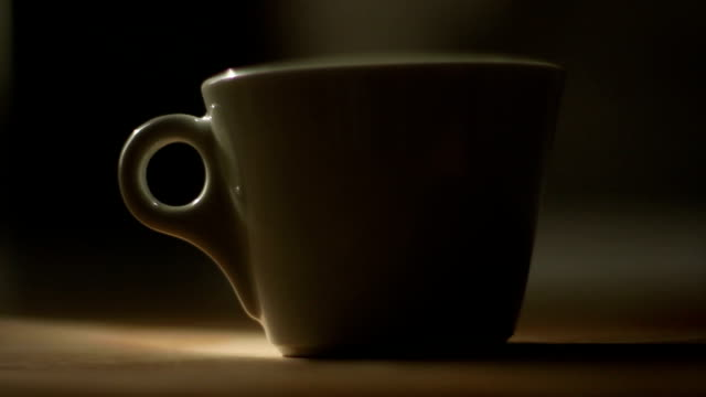 Dolly shot of a Coffee cup in dark scene video