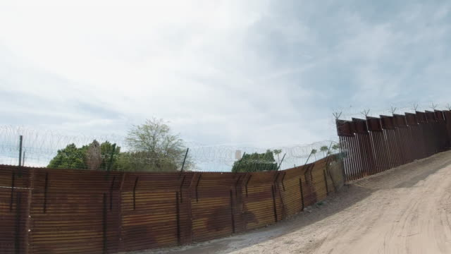Dolly Shot of a Dirt Road Running Parallel to Parts of the Old Wooden and New Steel-Slat Border Wall Topped by Razor Wire (on the US Side) between Mexico and the United States with the Town of Los Algodones, Mexico on the Other Side on a Partly Cloudy Day