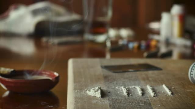 dolly skjuten av en rykande marijuana gemensamt med rader av droger och pengar - amfetamin pills bildbanksvideor och videomaterial från bakom kulisserna