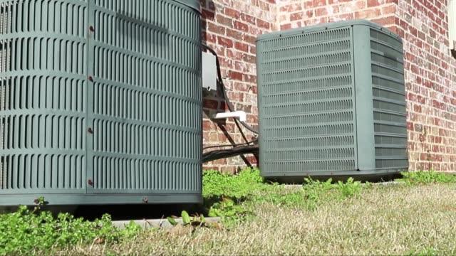 dolly shot of air conditioner units next to brick home - wyposażenie filmów i materiałów b-roll