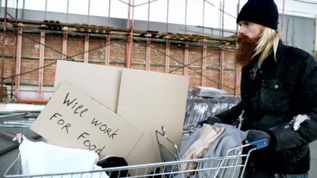 Dolly shot of Bearded homeless man walking down the street with shooping card at cold autumn day Bearded homeless man walking down street with shooping card at cold autumn day homeless person stock videos & royalty-free footage