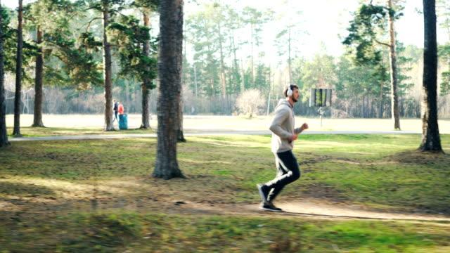 vídeos y material grabado en eventos de stock de tiro de carro de barbudo joven en chándal y zapatillas de jogging en el parque y escuchar música a través de auriculares modernos. concepto deportivo y milenio. - sudadera