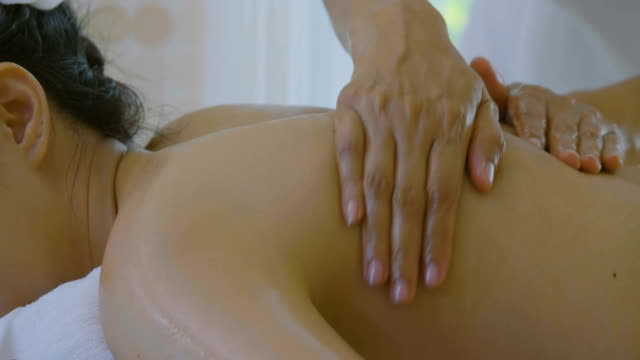 美しいアジアの女性マッサージを楽しんで治療エッセンシャル オイルのドリー ショット - エステ点の映像素材/bロール
