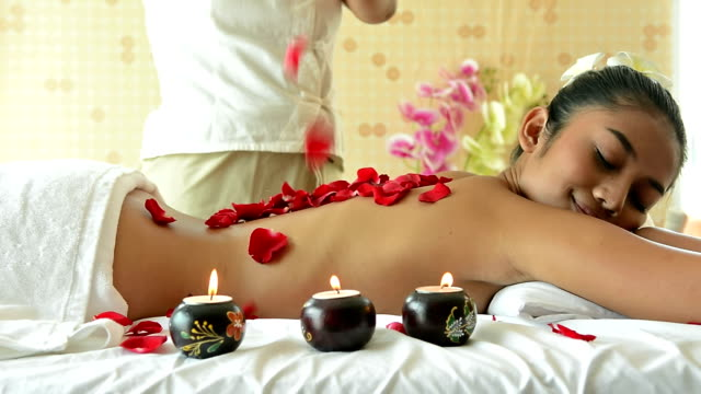 Video Dolly shot of beautiful woman having flower back massage by massage therapist on the massage bed in spa salon. Happy attractive girl with tropical flower relaxing and massaging in spa resort