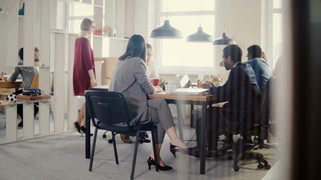 stockvideo's en b-roll-footage met dolly schot van mensen uit het bedrijfsleven brainstormen op moderne kantoor vergadering. gelukkig creatieve multi-etnisch personeel discussie 4k - marketing planning