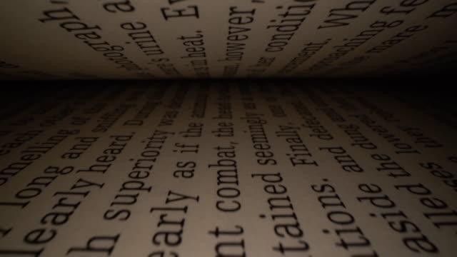 dolly sköt av kameran glider inuti boken mellan bokstäverna. latinska bokstäver och ord på en öppen bok med svart dramatisk bakgrund. utbildning, kunskapskoncept - lagbok bildbanksvideor och videomaterial från bakom kulisserna