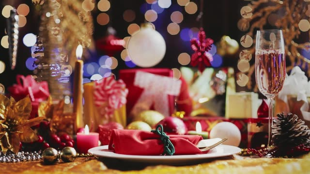 dolly shot of champagne flute on table with plate, gifts, and christmas decoration. christmas and new year celebration backgrounds. - cena natale video stock e b–roll