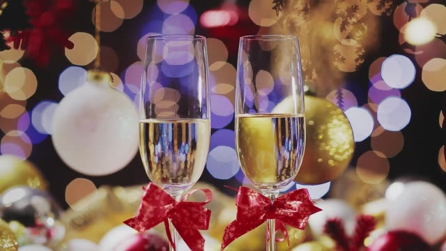 Dolly shot of Champagne flutes in table for two over golden holiday background. Christmas and New Year celebration Dolly shot of Champagne flutes in table for two over golden holiday background. Christmas and New Year celebration navidad stock videos & royalty-free footage