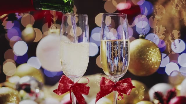 Dolly shot of Champagne flutes refilling in table for two over golden holiday background. Christmas and New Year celebration Dolly shot of Champagne flutes replenish in table for two over golden holiday background. Christmas and New Year celebration navidad stock videos & royalty-free footage