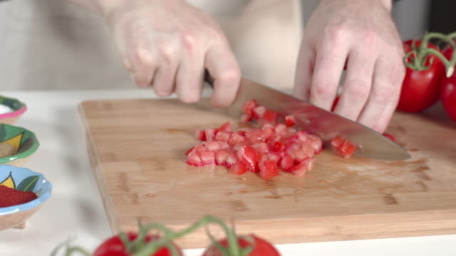 Dolly shot of chef dicing ripe tomato and transferring to large white bowl video