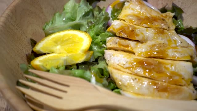 Dolly Shot of Chicken breast with fresh salad - arugula and sliced lemon and onion