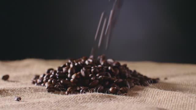 Dolly Shot Of Coffee Beans Falling On Hessian Sack 4K video