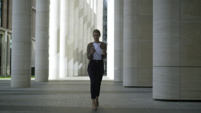 Dolly shot of confident young woman walking down street, reading and sending messages on her cell phone in slow motion