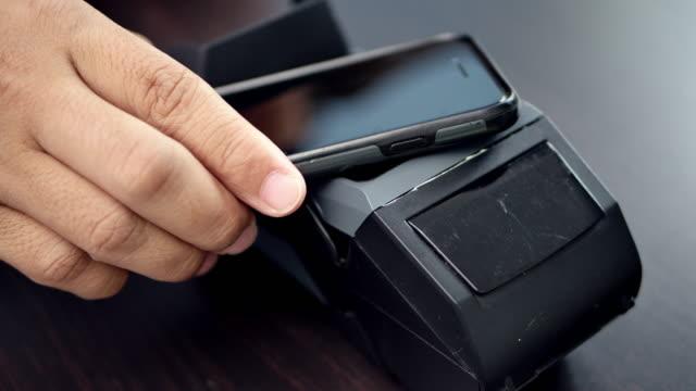 スマートフォンで非接触支払いを行う顧客のドリーショット。 ビデオ