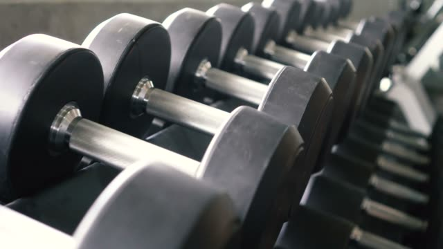 Dolly shot of dumbbells and barbells row in modern sport club gym