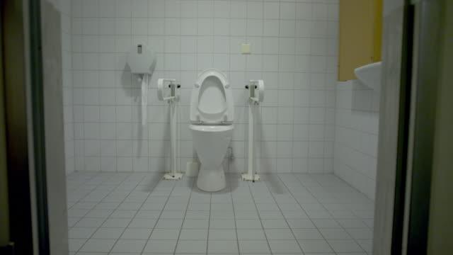 Dolly shot of empty public handicap bathroom