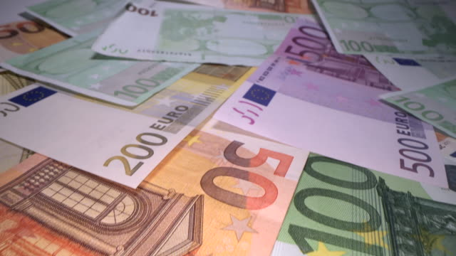 Dolly shot of euro bank notes background stacked on top of each other. Gliding through Euro money banknotes, pile of money, cash, stack of bills. Investing money, savings