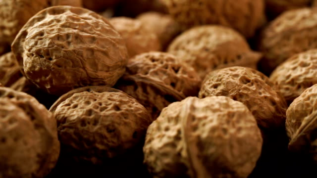 dolly shot of fresh walnuts on table - noci video stock e b–roll