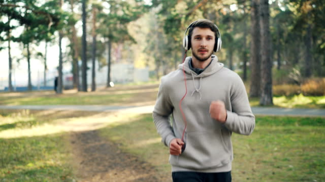 Dolly shot of good-looking bearded man with headphones running in park and listening to music on sunny autumn day. Modern technology and sports concept. Dolly shot of good-looking bearded man with headphones running in park and listening to music on sunny autumn day. Modern technology and active sports concept. sweatshirt stock videos & royalty-free footage