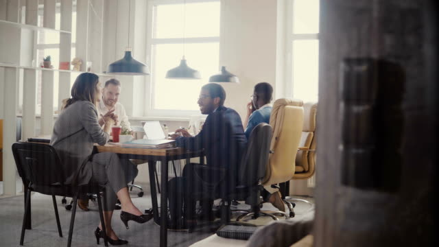 dolly shot of happy business partners discussion in modern office. multiethnic bosses collaborate on business project 4k - collega d'ufficio video stock e b–roll
