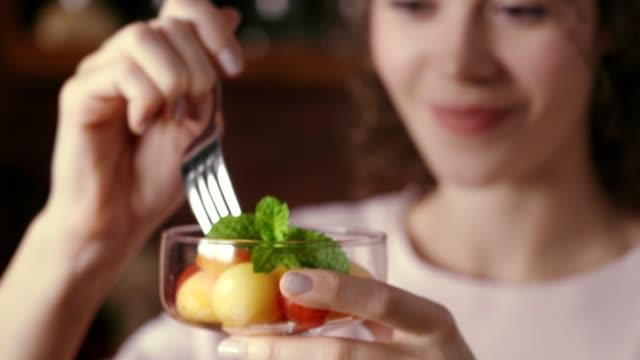 vídeos de stock, filmes e b-roll de dolly tiro do cabelo encaracolado hispânico mulher nova que come a salada de fruta em uma cozinha rústica - fruit salad