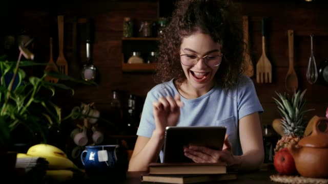 Dolly shot of Hispanic curly hair young woman shopping online using a digital tables in a rustic kitchen