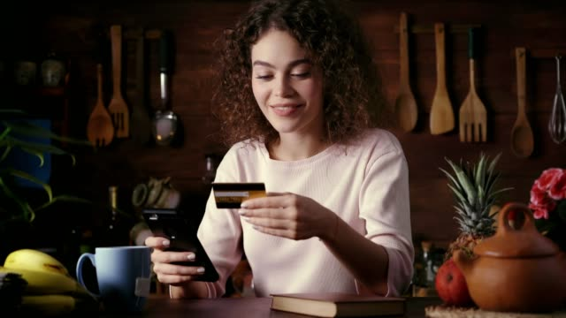 Dolly shot of Hispanic curly hair Young woman shopping online using smart phone in a rustic kitchen
