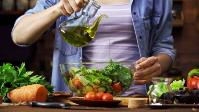 stockvideo's en b-roll-footage met dolly shot van hispanic jonge vrouw kruiden salade in rustieke keuken - oil kitchen