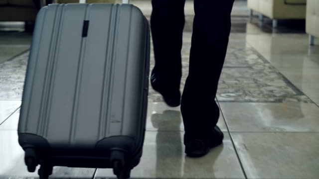 dolly shot of legs of businessman walking through hotel lobby pulling luggage and stop at reception desk. business, travel and people concept - hotel checkin video stock e b–roll