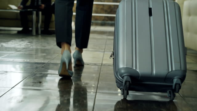 dolly shot of legs of businesswoman walking through hotel lobby pulling luggage and stop at reception desk. business, travel and people concept - hotel checkin video stock e b–roll