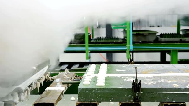 vídeos y material grabado en eventos de stock de dolly shot de metal látex almohada molde que se mueve fuera de la máquina con vapor de calor en la cinta transportadora en la fábrica de almohadas de látex - colchón