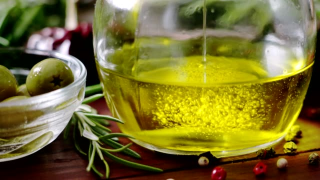 dolly shot of pouring olive oil into bottle in rustic kitchen with olives in pan - olio d'oliva video stock e b–roll