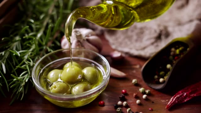 dolly shot of pouring olive oil on to olives in rustic kitchen - oliva video stock e b–roll