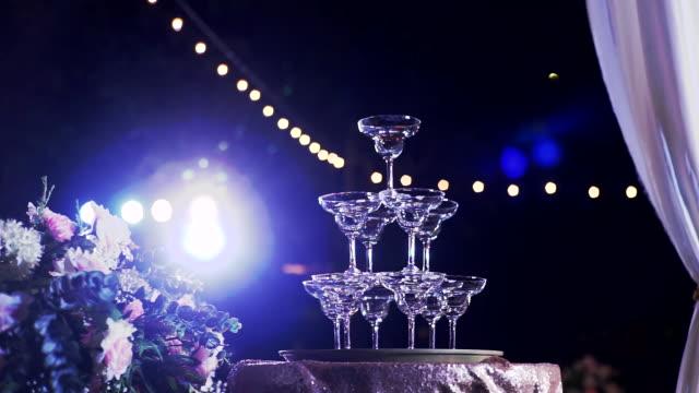 dolly schuss von pyramide von leeren champagner-gläser in hochzeitszeremonie mit beleuchtung im freien in der nacht. - teurer lebensstil stock-videos und b-roll-filmmaterial