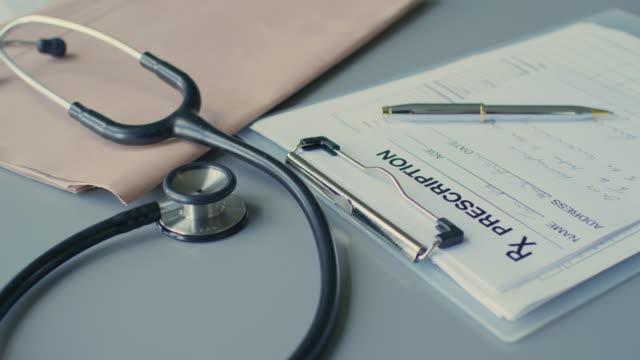 dolly shot of rx prescription on clipboard 4k - stetoscopio video stock e b–roll