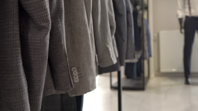 A dolly shot of the variety of male jackets in boutique. Close-up demonstration. Concept of luxury business fashion store