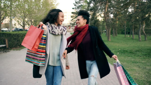 Dolly shot of two attractive mixed race women dancing and have fun while walking down the park with shopping bags. Happy young friends walk after visiting mall sale ビデオ