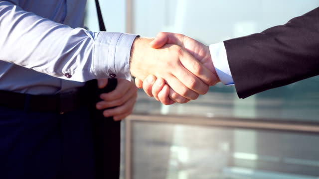 Dolly shot of two businessmen shaking hands after successful deal near office building. Close up of young colleagues congratulating each other in urban environment. Handshake of business partners