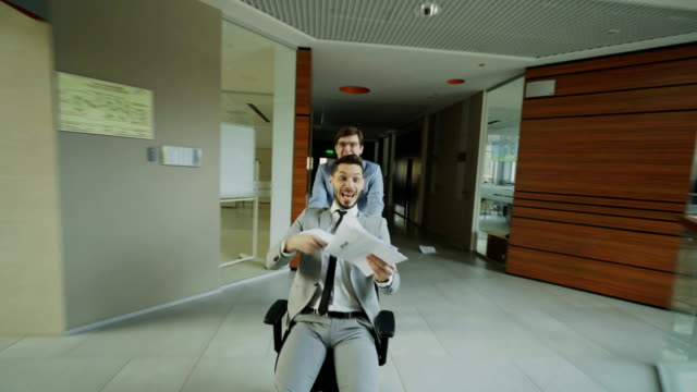 dolly shot of two crazy businessmen riding office chair and throwing papers up while having fun in lobby of modern business center - zabawa filmów i materiałów b-roll