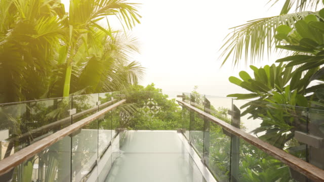 dolly shot of walking to the clear glass balcony that extends to take the sea view in pattaya, thailand. - terrazza video stock e b–roll