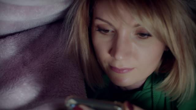 4k dolly shot av kvinnan tittar i telefonen under täcket - duntäcke bildbanksvideor och videomaterial från bakom kulisserna