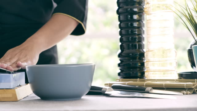 Dolly shot of woman putting water on stone and sharpening kitchen knife.
