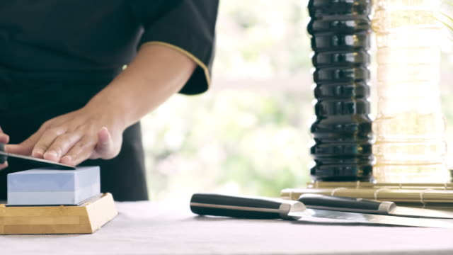 Dolly shot of woman sharpening kitchen knife.