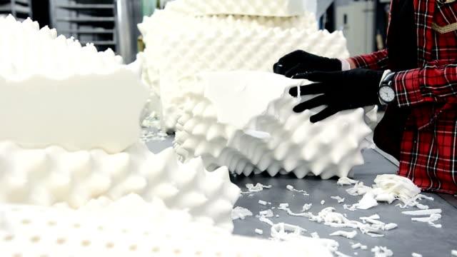 dolly colpo di donna che lavora nella linea di produzione di fabbrica di cuscini in lattice - gommapiuma video stock e b–roll