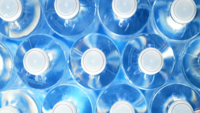 Dolly Shot Plastic Bottles For Recycling And Energy Saving High angle view of plastic water bottles in a row. Concept of industrial production, recycling, disposal of waste, and environmental conservation. Dolly shot. bottle stock videos & royalty-free footage