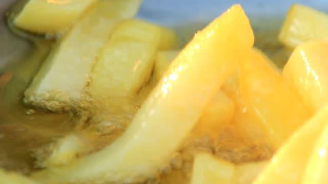 vidéos et rushes de chariot tiré des pommes de terre frites dans l'huile chaude - croustillant