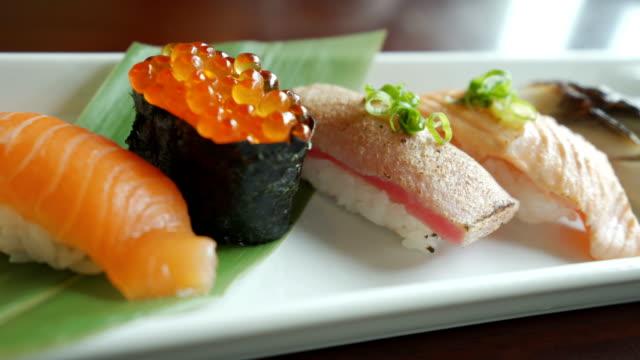 4k dolly schoss sushi in einer reihe aus nächster nähe - japanisches essen stock-videos und b-roll-filmmaterial