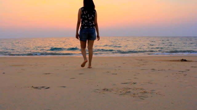 Dolly shot:Asian Woman walking on the sunset beach video