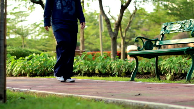 dolly shot: ragazza a piedi nel parco - giardino pubblico giardino video stock e b–roll
